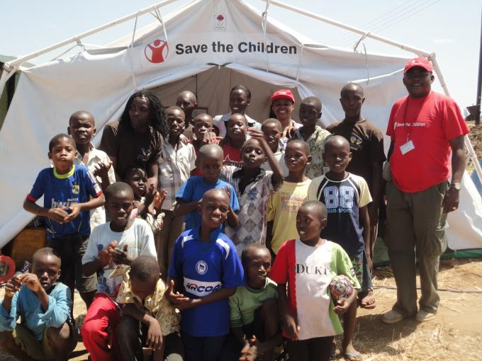 A group of children and Save the Children staff at a camp established by Save the Children for psychosocial counselling and hygienic support to children affected by floods in Dar es Salaam at Mabwepande, outskirt of Dar es Salaam.