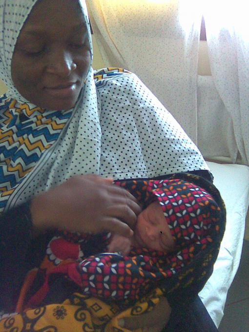 One among the mothers, holding her child who was born in a Health Care Unit